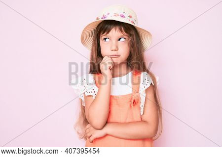 Little caucasian kid girl with long hair wearing spring hat thinking concentrated about doubt with finger on chin and looking up wondering