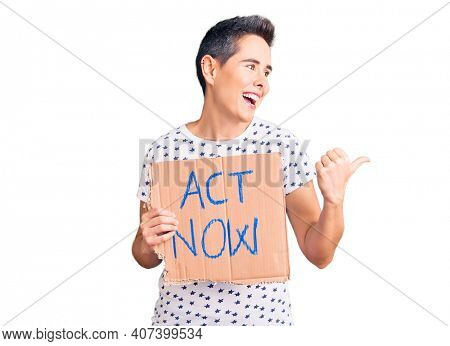 Young woman with short hair holding act now banner pointing thumb up to the side smiling happy with open mouth