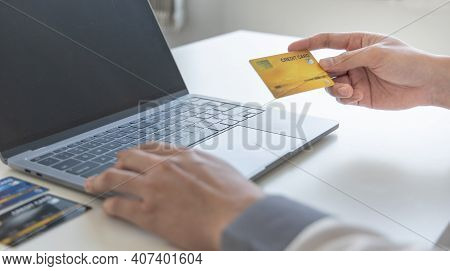 Online product purchase, Businessman use laptop register via credit cards to make online purchases,