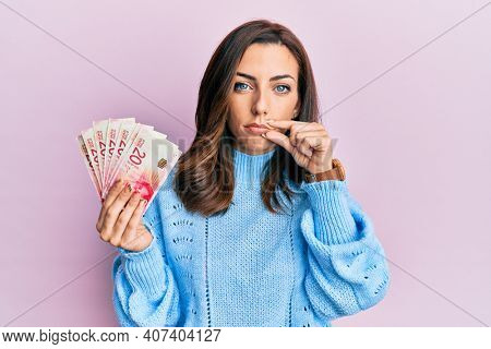 Young brunette woman holding 20 israel shekels banknotes mouth and lips shut as zip with fingers. secret and silent, taboo talking