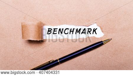 Torn Kraft Paper, White Background With The Text Benchmark. Nearby Is A Black Handle. View From Abov