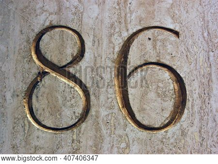 The Number Eighty Six Carved Into Marble And Gilded On The Side Of A Large Building Overlooking A Pa