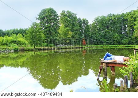 Woman Enjoying Rest Lying On Shore Of Forest Lake. Pretty Woman Relaxing At Riverside. Girl Enjoying