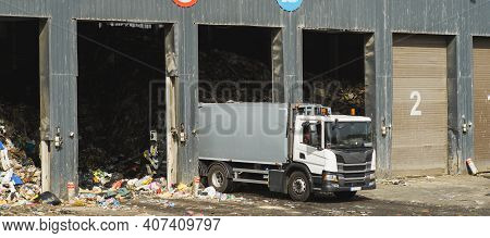 White Garbage Truck Near Gates Of Warehouse Of Garbage. Waste Sorting. Recycling. Caring For Environ