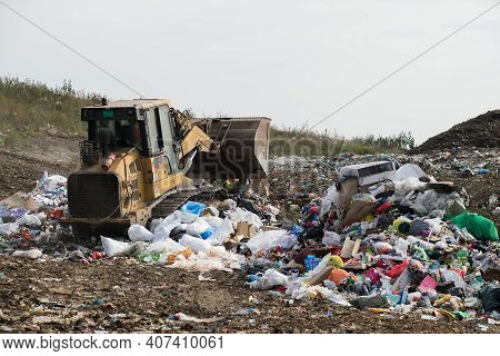 Environmental Pollution. Huge Landfill Of Big City. Yellow Tractor. Waste Sorting. Caring For Enviro