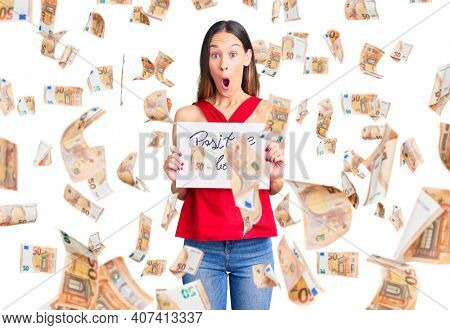 Beautiful brunette young woman holding positive vibes banner scared and amazed with open mouth for surprise, disbelief face