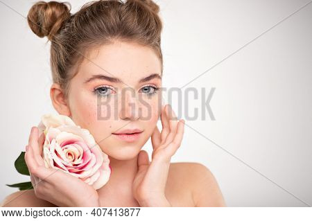 Beautiful young  woman with healthy skin face. Skin care concept. Closeup female face with a freckled. Women's face with flower Teenage girl with a clean skin of face, isolated.