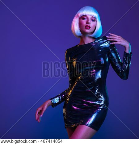 Full-length portrait of beautiful  fashionable woman in shining dress, space concept. Art portrait  of  an young attractive model.  Stylish blonde in shiny dress. Fantasy style. Glamour fashion girl