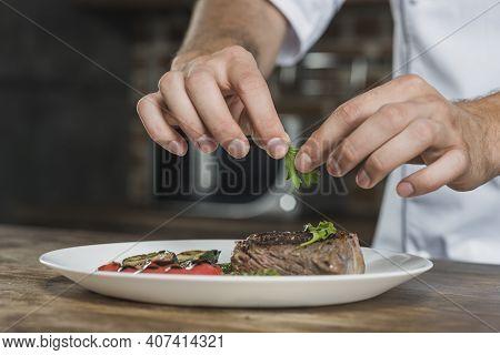 Chef Male's Hand Garnishing The Coriander On Prepared Roasted Beef
