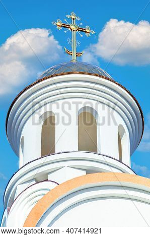 Golden Dome Of Russian Orthodox Church With Cross Against Blue Sky
