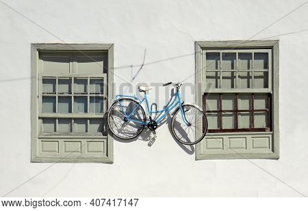 Retro Bicycle On Exterior Wall Of Cement Facade. Two Old Closed Sash Windows On White Facade And Han