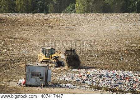 Yellow Tractor Loader Works On Huge Landfill Of Big City. A Lot Of Garbage On Dump Near Forest. Wast