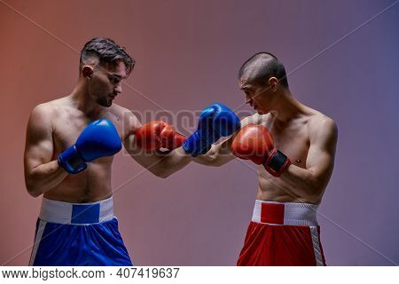 Wrestling Of Two Fighting Guys With Fit Torsos In Boxing Gloves In Red Light In Studio, Martial Arts