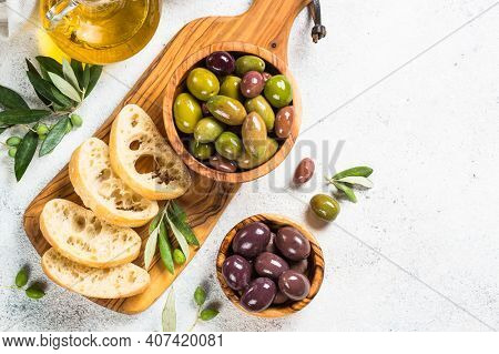 Olives In Wooden Bowls, Ciabatta Bread And Olive Oil Bottle On White Background. Top View With Copy