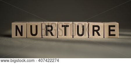 A Wooden Blocks With The Word Nurture Written On It On A Gray Background.