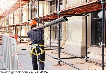 builder carries a steel beam on his shoulder. Construction site, building construction and reconstruction process. Construction site safety, scaffolding