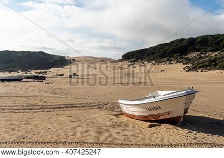 Bolonia, Spain - 27 January, 2021: Small Wooden Fishing Rowboats On A Sandy Beach With A Large Sand