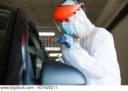 Medical Worker In Personal Protective Equipment Swabbing A Person In A Car Drive Through Coronavirus
