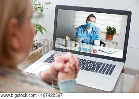 Young Gp Physician And Elderly Female Patient Consulting Over Video Call,virtual Medical Health Chec