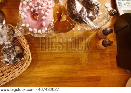 Doughnuts With Various Glaze And Bakery Products On A Wooden Surface. Flat Lay Composition With Copy