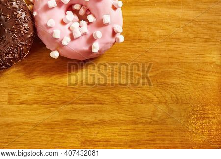 Doughnuts With Various Glaze On A Wooden Surface. Flat Lay Composition With Copy Space On A Wooden B