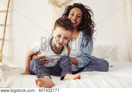 Young Pretty African Americam Mother With Son In Bed At Morning Playing, Happy Family, Lifestyle Peo