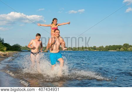 Happy Family - Father, Son, Little Daughter Run Together Along The Beach. Lifestyle, Travel, Vacatio