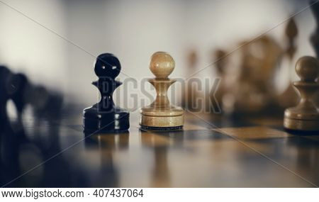 Two Chess Pieces Are Pawns: Black And White. Wooden Chess Pieces On The Chessboard. Intellectual Gam