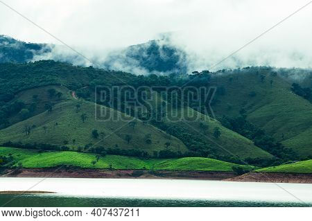 Mountains Next To A Lake With Clouds Evaporating At The Hilltop After A Rainfall During The Afternoo