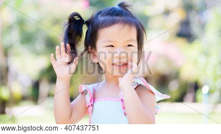 Candid Happy Asian Girl Running In The Park. Child Has A Sweet Smile. Children Wears A Mint Green Sh