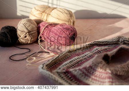 Fragment Of Warm Striped Raglan Sweater On Pink Concrete Background.