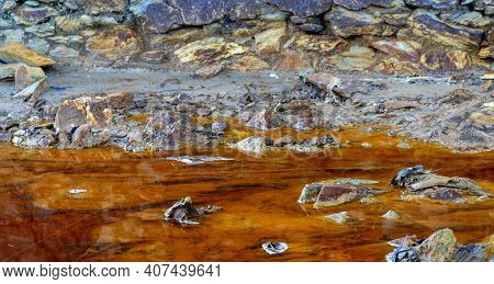 Close Up Of Orange Red River With Iron Ore And Copper Ore Deposits In The Rio Tinto Mining Area