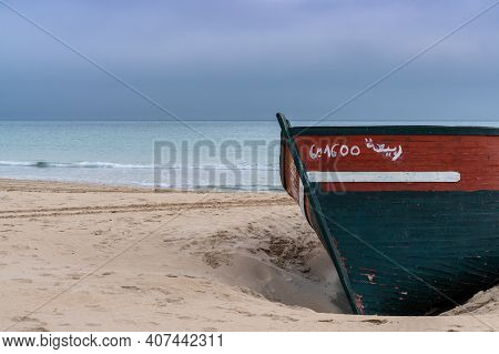 Colorful Wreck Of An Old Wooden Rowboat Buried In The Sand With An Overcast Sky And Ocean Behind