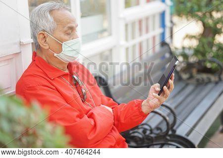 Asian Old Elder Senior Man Wearing Face Mask Elderly Using Mobile Smart Phone Cellphone. Mature Reti