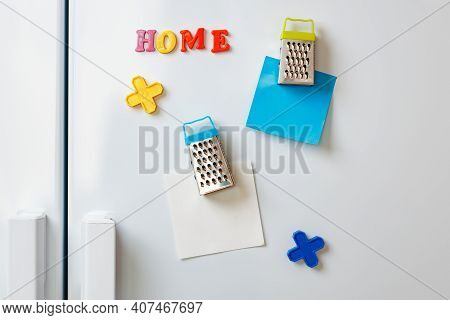 Sheets Of Paper And Magnets On Fridge Door In Kitchen