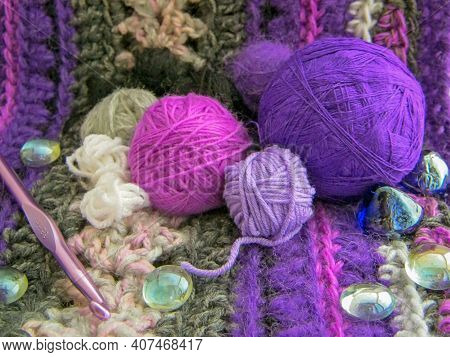 Crochet Knit Thick Yarn Hobby Background. Yarns Purple Colors On Blanket With Crochet Hook. Knitting
