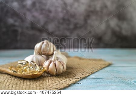 Capsule Garlic Oil In Wooden Spoon With Fresh Garlic On The Old Wooden Table, The Benefit Of Garlic