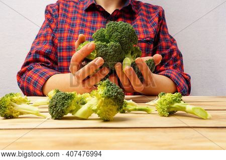 Fresh Broccoli. A Girl In A Red Plaid Shirt Holds Broccoli In Her Hands