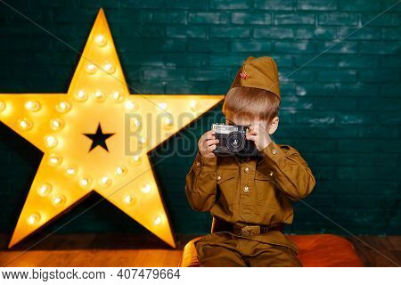 Soldier With Film Camera. Photographer With Camera In His Hands. Child War Correspondent During The