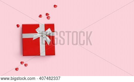 Red Gift Box With Silver Bow On Pink Background With Red Hearts Around.