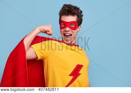 Crazy Young Man In Superhero Costume Looking At Camera With Opened Mouth And Showing Bicep Against B