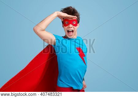 Excited Young Man In Superhero Costume Holding Hand Near Forehead And Looking At Camera With Opened