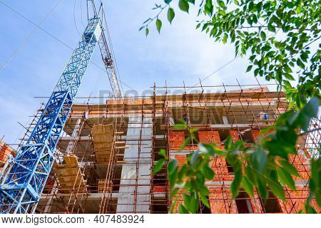 Scaffold And Crane Are Placed Against Unfinished Edifice, Building Under Construction.