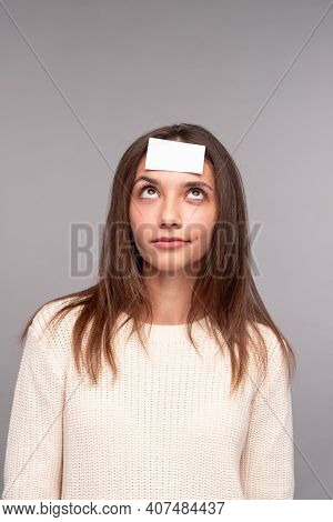 Pensive Perplexed Young Brunette In Casual Wear With White Sticky Paper On Forehead Playing Who Am I