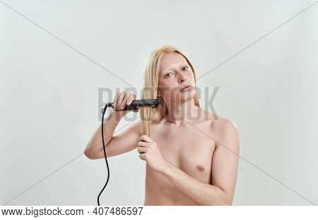 Young Caucasian Long Blond Haired Man Applying Hair Straightener While Standing On White Background
