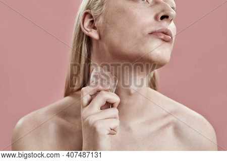 Young Caucasian Guy With Long Fair Hair Using Quartz Tool For Neck Massage While Standing On Pink Ba