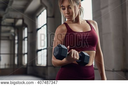 Young Sporty Woman Exercising With Dumbbell While Training Bicep Muscles During Fitness Workout In G