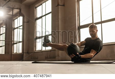 Side View Of Muscular Male Athlete Doing Abs Exercise With Ball During Intense Fitness Workout In Gy