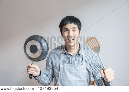 Man Asian Cooking In Kitchen Of Home He Holds Bowl And  Spatula  To Great Hand On Microwave In Kitch