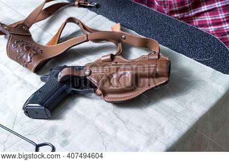 A Pistol In A Leather Holster. The Gun Is On The Table. Top.